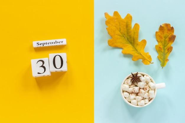 30 september, kopje cacao met marshmallows en gele herfstbladeren op gele blauwe achtergrond.