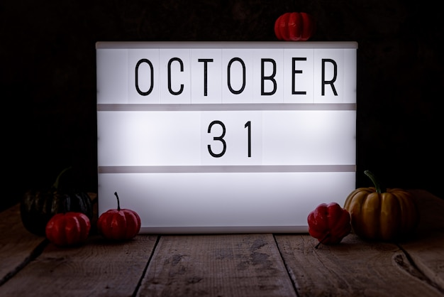 31 oktober lichtbak in de donkere kamer met pompoenen op houten vloer