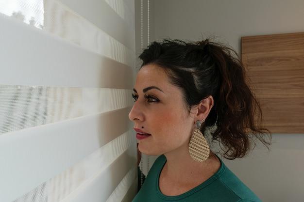 35-jarige braziliaanse vrouw kijkt door het gordijn.