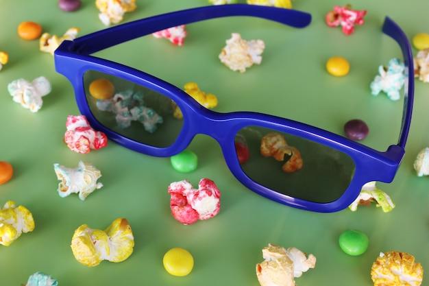 3d-bril voor het kijken naar film en gekleurde popcorn op groene achtergrond.