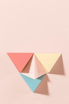 3d pastel piramide papier ambacht op een roze achtergrond