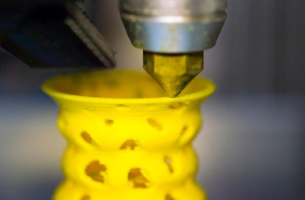3d-printer drukt af van de plastic figuurclose-up. 3d-printer maakt gele modelclose-up op grijs vlak oppervlak