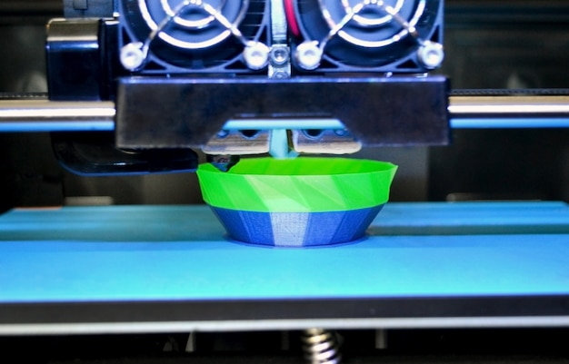 3d-printer werkt en maakt een object van de close-up van hete gesmolten plastic. automatische driedimensionale 3d-printer voert plastic modelleringsprototype uit in het laboratorium.