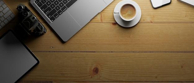 3d-rendering werkruimte met laptop koffiekopje camera tablet en kopieer ruimte op houten tafel