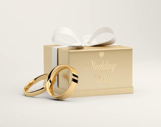 3d-weergave van een gouden geschenkdoos met een wit lint en gouden ringen
