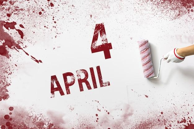 4 april. dag 4 van de maand, kalenderdatum. de hand houdt een roller met rode verf vast en schrijft een kalenderdatum op een witte achtergrond. lente maand, dag van het jaar concept.