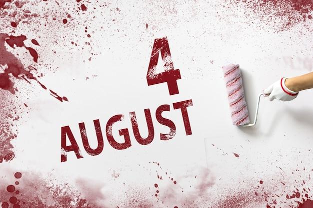 4 augustus. dag 4 van de maand, kalenderdatum. de hand houdt een roller met rode verf vast en schrijft een kalenderdatum op een witte achtergrond. zomermaand, dag van het jaarconcept.