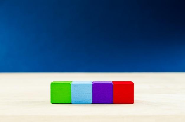 4 gekleurde houten blokken geplaatst in een rij, met kopie ruimte, over blauwe ruimte.