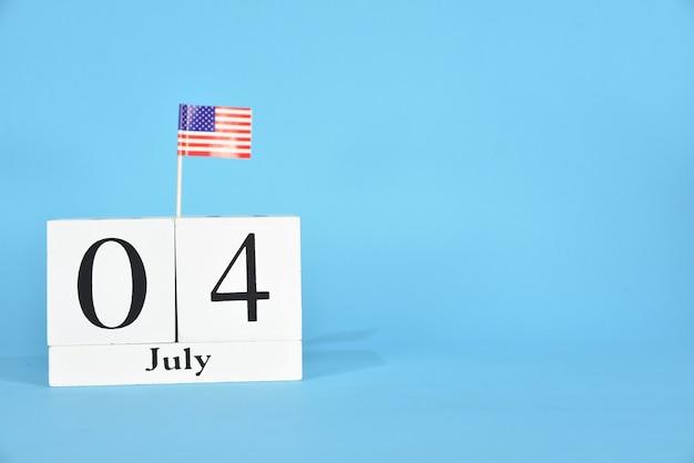 4 juli tekst houten blok kalender en amerikaanse vlag op blauw