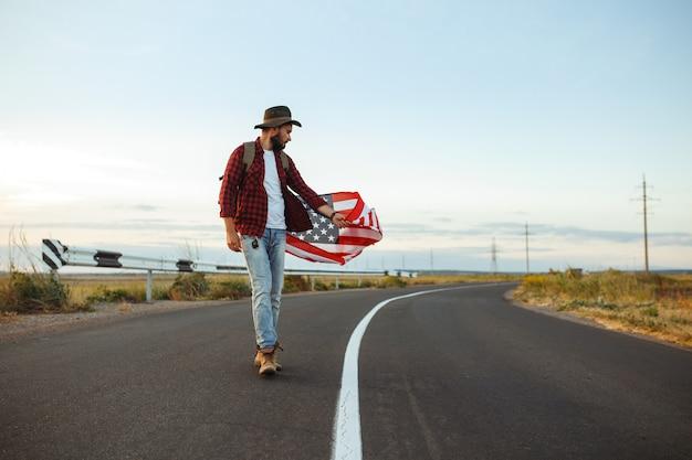 4 juli. vier juli. amerikaan met de nationale vlag. amerikaanse vlag. onafhankelijkheidsdag. patriottische vakantie. de man draagt een hoed, een rugzak, een overhemd en een spijkerbroek.