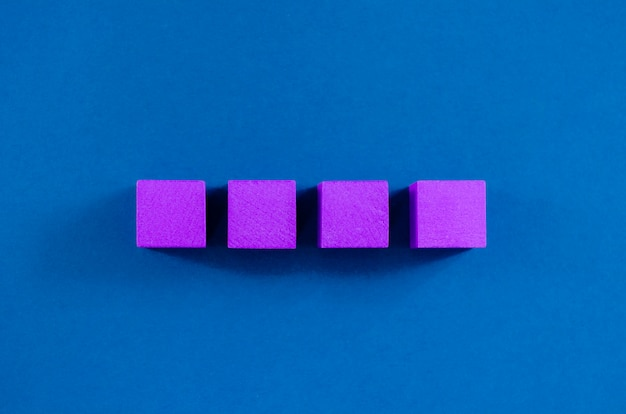 4 paarse houten blokken in een rij geplaatst, met kopie ruimte, over blauwe ruimte.