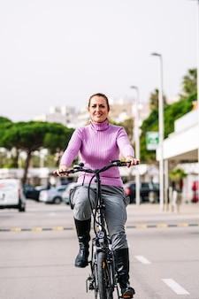 40-jarige vrouw rijdt op haar elektrische fiets door de straten van de stad (concept van elektrische mobiliteit)