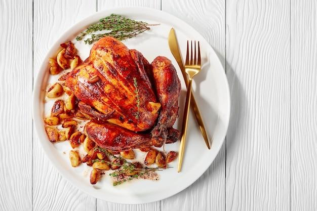 40 kruidnagel kip in een witte schotel op een houten tafel, franse keuken, horizontale weergave van bovenaf, plat leggen, close-up, vrije ruimte
