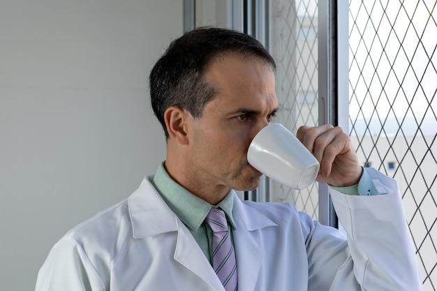 44-jarige dokter met witte jas en stropdas koffie drinken en uit het raam kijken.
