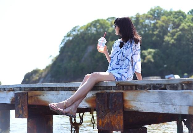 45 jaar oude russische vrouw die limonade drinkt en op de pier zit