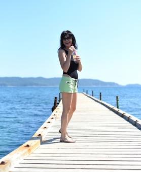45 jaar oude russische vrouw die limonade drinkt en op een pier staat