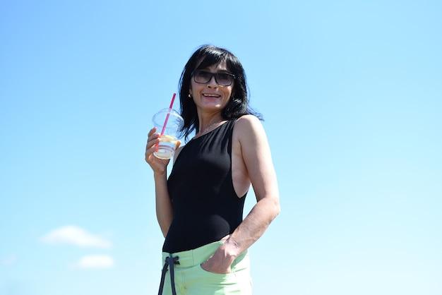 45 jaar oude russische vrouw die limonade drinkt en tegen de blauwe lucht staat