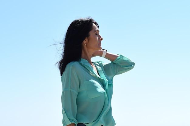 45 jaar oude russische vrouw die tegen de blauwe lucht staat