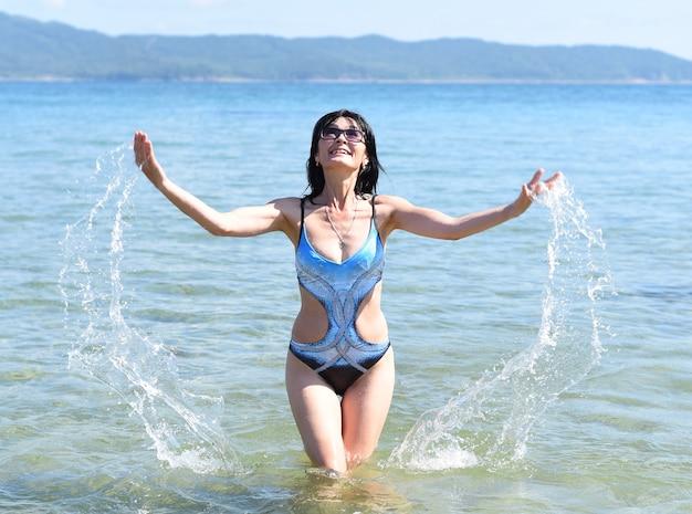 45 jaar oude russische vrouw in zwempak lachend en staand in japanse zee
