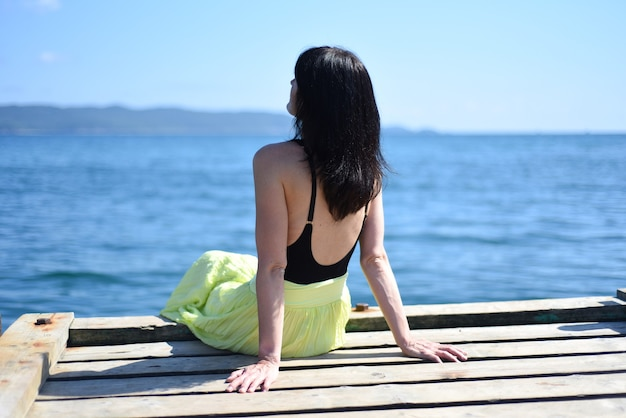 45 jaar oude russische vrouw zittend op een pier en wegkijkend tegen de japanse zee