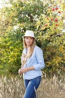 45-jarige vrouw in een blauw shirt en hoed poseren in een appelboomgaard