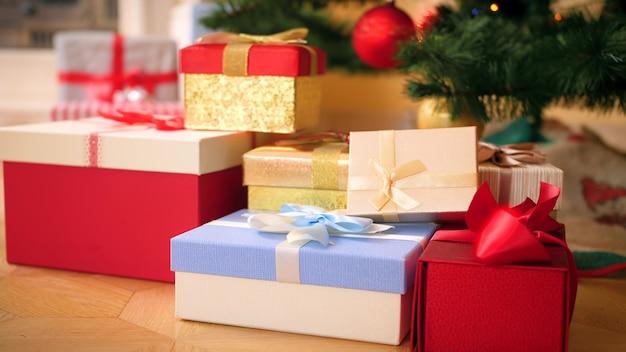 4k-beelden van camera die langzaam zoemt op grote hoop kerstcadeaus en cadeautjes die op de vloer onder de kerstboom liggen. perfecte foto voor uw wintervakanties en vieringen