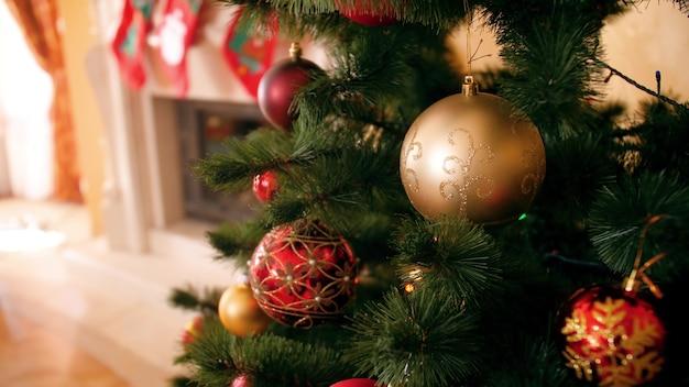 4k close-up beelden van camera langzaam pannen over prachtige kerstboom versierd met kleurrijke kerstballen en gloeiende lichtslingers in woonkamer bij huis