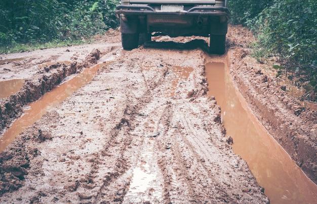 4x4 offroad wielclose-up in een plattelandslandschap in een bos met een modderige weg