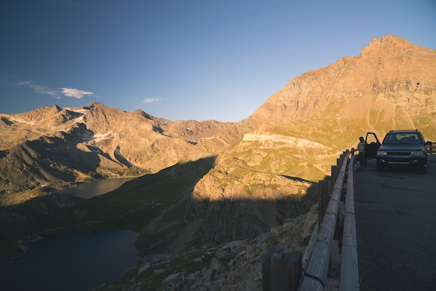 4x4 suv geparkeerd op weg op panoramisch uitzicht punt op de italiaanse alpen. eén persoon kijkt naar uitzicht. kleurrijke hemel bij zonsondergang, gestemd beeld.