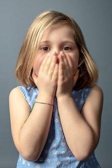 5 éénjarigen kaukasisch meisje met handen die haar gezicht behandelen.