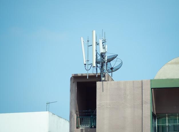 5 g mobiele telefoontoren voor mobiele communicatie en satelliet-tv-schotel geïnstalleerd op het gebouw