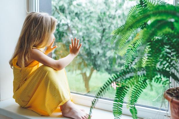 5 jaar oud blond meisje dat uit het raam staart op een natte koude regenachtige dag.