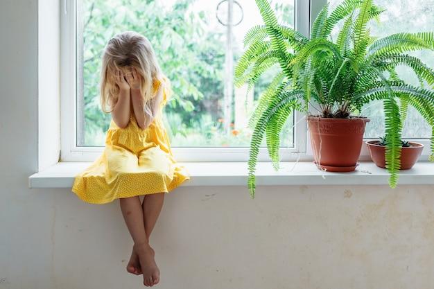 5 jaar oud blond meisje zit op de vensterbank en huilt en bedekt haar gezicht met haar handen