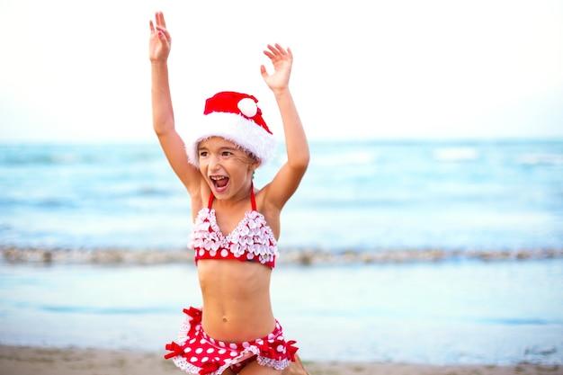 5-jarig meisje in rode zwembroek en kerstmuts op het strand is blij, schreeuwt, springt en zwaait met de handen van geluk. kerst- en nieuwjaarswintertochten naar warme landen. toerisme voor vakanties in de tropen