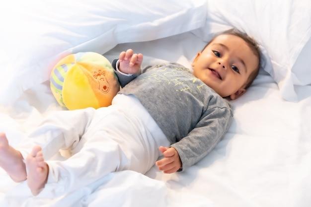 5 maanden oude blanke baby glimlachend in wit bed net wakker geworden