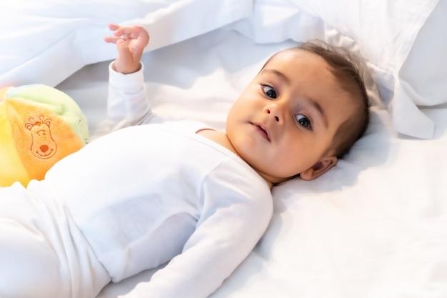 5 maanden oude blanke baby glimlachend in wit bed net wakker, witte bodysuit en een bal om te spelen