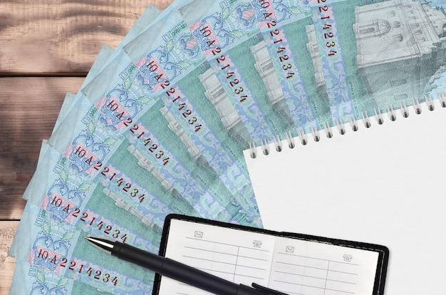 5 oekraïense hryvnias-rekeningenventilator en notitieblok met contactboek en zwarte pen
