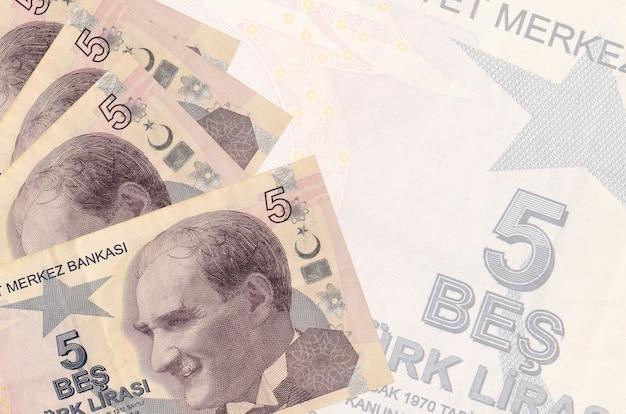 5 turkse lirasrekeningen liggen in stapel op achtergrond van groot semi-transparant bankbiljet.
