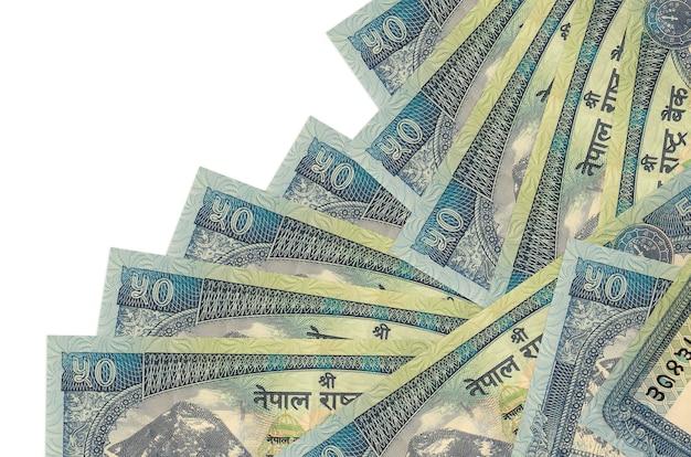 50 rekeningen van nepalese roepies liggen in verschillende volgorde geïsoleerd op wit