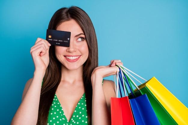 50% verkoop. close-up foto van positief vrolijk meisje sluit dekking oog gezicht debetkaart look copyspace droom draag groen gestippeld crop singlet tanktop geïsoleerd over blauwe kleur achtergrond