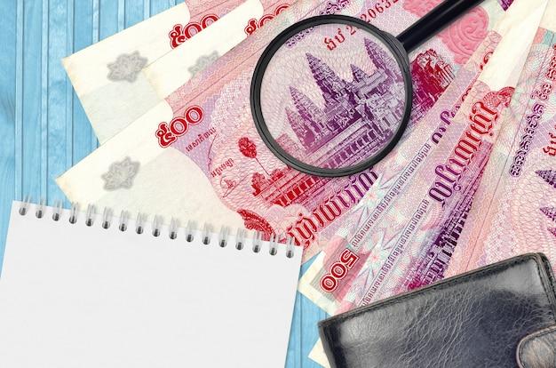 500 cambodjaanse riels biljetten en vergrootglas met zwarte portemonnee en notitieblok