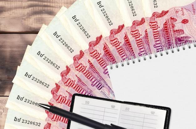 500 cambodjaanse riels-biljettenventilator en notitieblok met contactboekje en zwarte pen