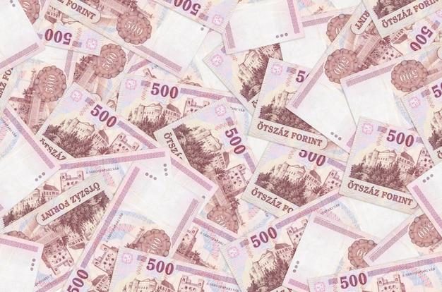 500 hongaarse forintbiljetten liggen op een grote stapel. veel geld