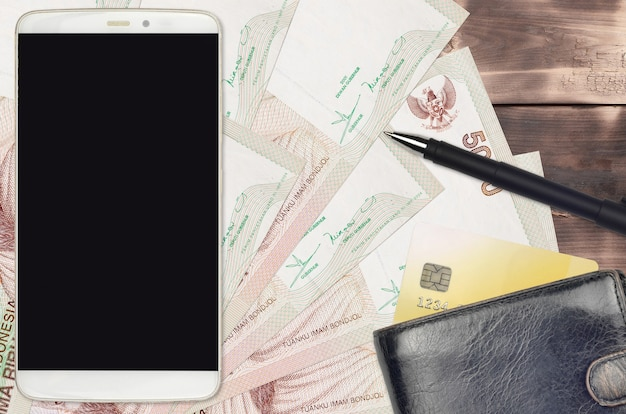 5000 indonesische roepia-rekeningen en smartphone met portemonnee en creditcard. e-betalingen of e-commerce concept. online winkelen en zakendoen met draagbare apparaten