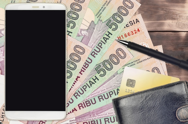 5000 indonesische roepia-rekeningen en smartphone met portemonnee en creditcard.