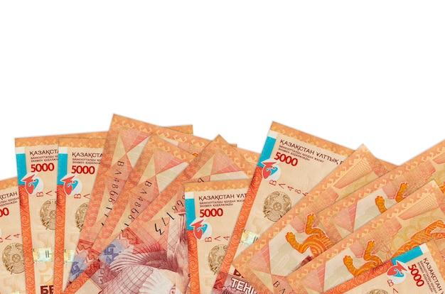 5000 kazachse tenge-rekeningen liggen aan de onderkant van het scherm geïsoleerd op een witte muur met kopie ruimte.
