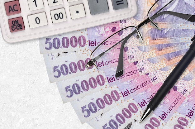 50000 roemeense leu facturen ventilator en rekenmachine met bril en pen. zakelijke lening of belastingbetaling seizoen concept. financiële planning