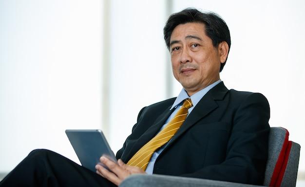 50s aziatische senior executive zakenman zittend, comfortabel leunend achterover op de bank in binnen kantoor of werkplek, tablet gebruiken om te werken, glimlachen, lachen met succes. zaken, technologieconcept.