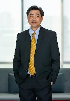 50s oude aziatische senior executive zakenman, gekleed in een formeel pak met luxe stropdas, staande in een binnenkantoor, hand in broekzak, camera kijkend, glimlachend met tevredenheid, vertrouwen.