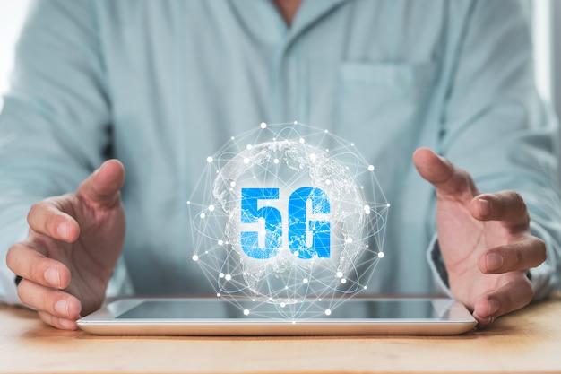 5g en internet of thing of iot-concept, zakenman die virtuele 5g wereldwijde netwerken op tablet beschermt.